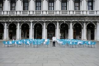 A waiter stands by empty tables outside a restaurant at St Mark's Square after Italy's government adopted a decree with emergency new measures to contain the coronavirus, in Venice. March 5, 2020.
