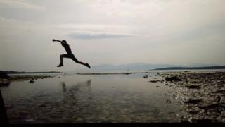 boy leaping over water