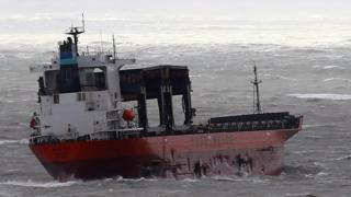 Visible damage along hull of cargo ship