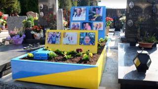 A picture showing the grave of Carlo Annoni, a large blue and yellow structure covered in pictures of him.