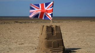 Union Jack flag sits on top of a sand castle on a beach