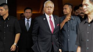 Malaysia' Prime Minister Najib Razak (C) reacts as he walks towards his car after attending a parliamentary session in Kuala Lumpur on 26 January 2016