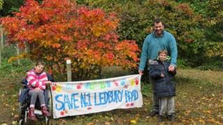 """Gwen and Fergus and their father Ben holding a """"Save No 1 Ledbury Road"""" banner"""