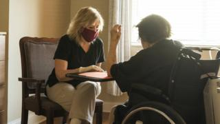 Care worker in mask and gloves