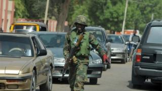 An officer of the Joint Military Task Force (JTF) walks on the road in the northeastern Nigerian town of Maiduguri, Borno State , on April 30, 2013.