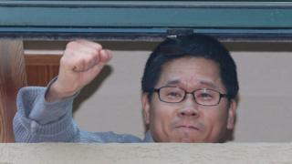 Han Sang-gyun raises his fist through a window of a building at the Jogye Temple on 1 December