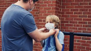 father putting mask on son in school uniform