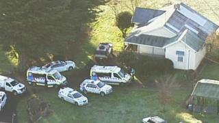 Police and ambulance vehicles outside the house where the dog attack took place