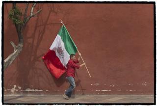 Bandera mexicana flamea en las manos del escritor español Ignacio Martínez de Pisón