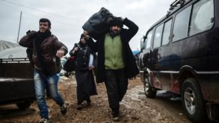 Syrian refugees arrive near the Turkish border, after fleeing fighting in Aleppo, 6 February