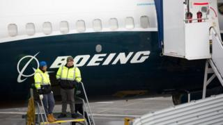 Workers standing next to a grounded Boeing 737 Max 9 aircraft