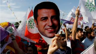 "A supporter of the pro-Kurdish Peoples"" Democratic Party (HDP) holds a mask of their jailed former leader and presidential candidate Selahattin Demirtas during a rally in Ankara, Turkey, June 19, 2018"