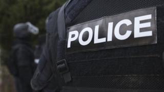 Image shows a close up of the 'Police' patch on the back of a police officer's jacket.