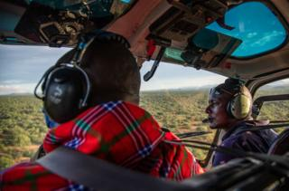 Ambrose Ngetich and Captain Iltasayon Neepe look out from the cockpit of a helicopter