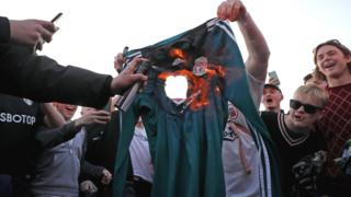 Fans burn a Liverpool shirt outside Elland Road