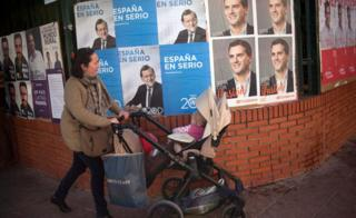 A woman walks past election posters in southern Spain (file pic)