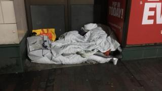 Picture of homeless woman in Northampton under wet bedding.