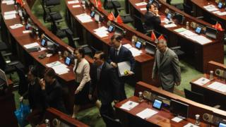 Pro-Beijing legislators walk out of the main chambers in protest against the second swearing-in of pro-independence lawmakers