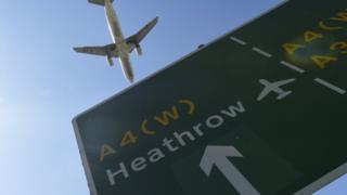 Plane flies over Heathrow road sign