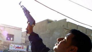 An Iraqi shoots celebratory gunfire in the southern city of Nasiriyah (14 December 2003)