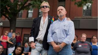 Pareja homosexual con una pequeña bandera del movimiento gay