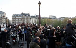 People gather on a bridge to watch the blaze