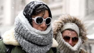 Dos mujeres cubiertas de nieve en Reino Unido.