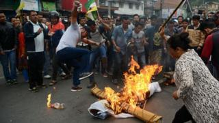 Indian supporters of the separatist Gorkha Janmukti Morcha (GJM) group shout slogans while burning an effigy of West Bengal Chief Minister Mamata Banerjee during an indefinite strike called in Darjeeling on June 19, 2017.