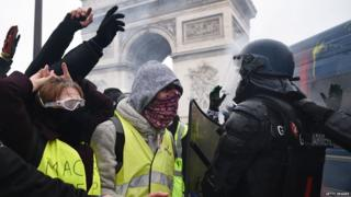 Masked protesters confront police near the Arc de Triomphe, Paris (1 December)