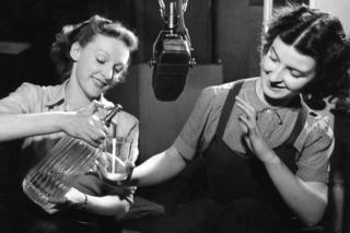 Elaine Cunningham and Monica Bell squirting soda water into a glass to create sound effects for 'noises off' during the war when women were used to fill jobs left vacant by the men who had gone to fight, 1942.