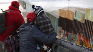 Izbeglice na granici Meksika i SAD gledaju preko ograde