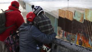Members of the migrant caravan look over the U.S.-Mexico border fence on November 30, 2018 in Tijuana, Mexico