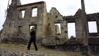 Um visitante passa pelas ruínas da vila mártir francesa de Oradour-sur-Glane, perto de Limoges, 6 de agosto de 2013
