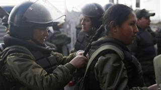 Female police in full riot gear braid each other's hair before in La Paz, Bolivia, on 22 July 2015