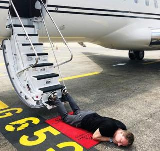 A man lying on a runway his legs strewn on the steps of a private jet
