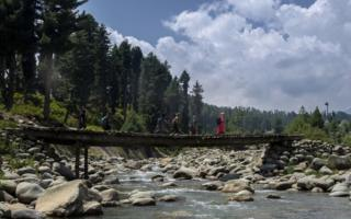 Students walking to school on a bridge in Kashmir.