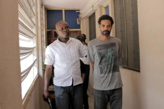 Police officer escorts Arthur Simpson-Kent (right) inside the Criminal Investigation Department headquarters in Accra, Ghana, on 10 January 2016