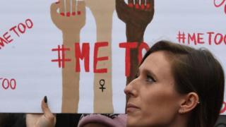 سيدة تحمل لافتة لمناهضة التحرش الجنسي