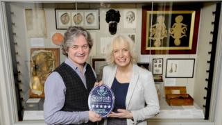 Manuela Calchini (R), presents Chris Henry (L) with five stars plaque