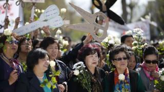 巴黎共和國廣場悼念劉少堯集會現場一群婦女舉起剪刀形標語牌(2/4/2017)