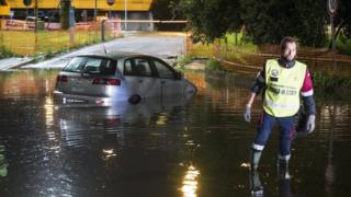 An Italian policeman wades in a flooded street near an abandoned car