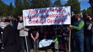 протестующие против папы в Грузии с плакатом