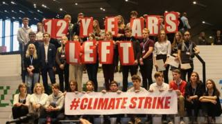 محتجون يرفعون شعارات خلال مؤتمر المناخ