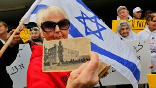 Holocaust survivor Malkah Gorka holds a picture from her school days in Poland during a protest in front of Polish embassy in Tel Aviv on February 8, 2018