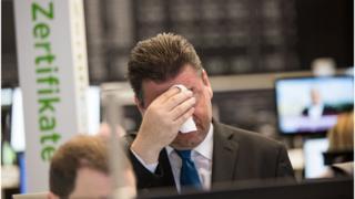 Trader Robert Halver of Baader Bank wipes his brow as the Frankfurt stock exchange falls (24 June)