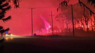 A night sky lit a dark red from a bushfire at the coastal village of Harrington in New South Wales on 29 October