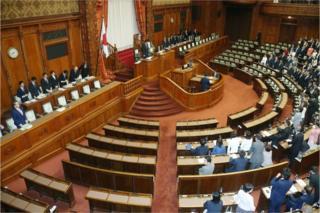 参議院の与党議員たちが起立して新法に賛成した(15日午前)