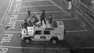 CCTV image of the group of men and the police vehicle
