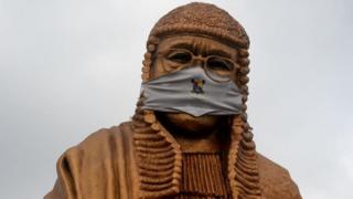 The statue of late lawyer and rights activist Gani Fawehinmi wears a face mask at the Liberty Park at Ojota in Lagos, on July 27, 2020. - The 34-feet statue to immortalise the fiery lawyer and rights advocate is being used to sensitise people to the sanitary measures taken to curb the spread of the COVID-19 pandemic in Lagos, Nigeria's commercial hub and epicentre of the virus in the country.