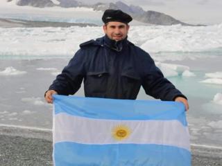 Marinheiro com bandeira da Argentina em frente a uma geleira